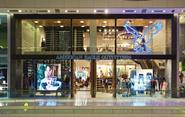 In the Westfield London store a vast blue neon eagle dominates the high glass frontage, drawing the eye upwards so the shopper gets a view of both floors and the staircase that connects them.