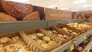 Aldi\'s bakery section is stocked with wicker baskets and a sign stating 'baked fresh today'.