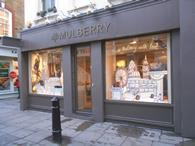 Luxury retailer Mulberry has reported a slump in full-year pre-tax profits, but said it has seen a \'positive uplift\' in sales since November.