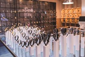 72 watches are displayed on plinths, parts of which sit below the surface of an under-lit tank